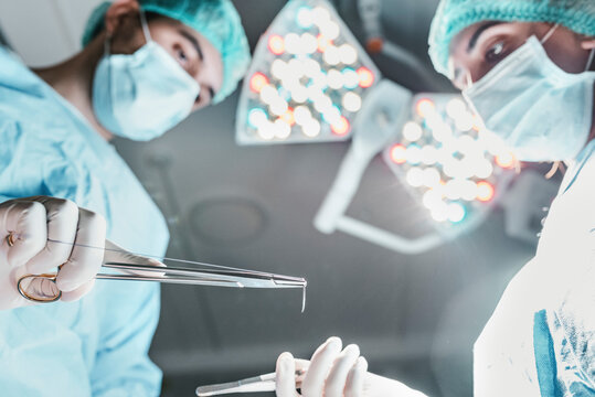 From below side view of focused professional surgeon and nurse with medical scissors working together in operating room in modern hospital