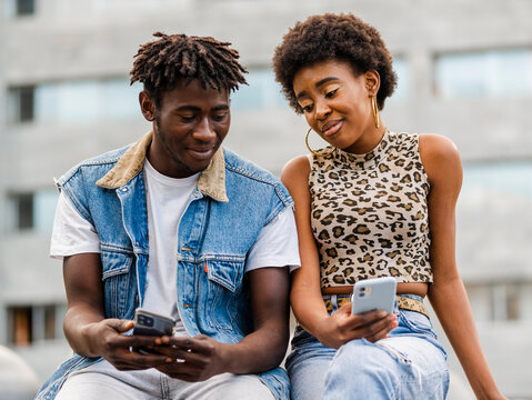Cheerful young African American man and woman with curly hair dressed in trendy ripped jeans sitting on fence browsing on smartphone while spending time together in city