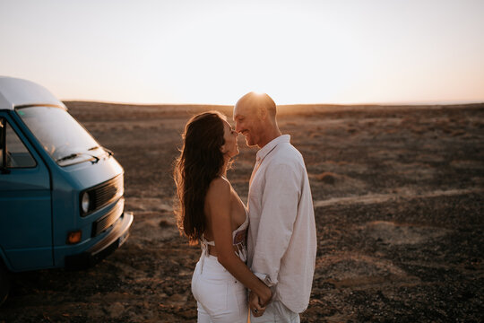 Side view of traveling couple standing near van in savanna and gently kissing on background of sunset sky