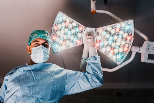 From below of serious male surgeon in protective mask and medical uniform adjusting surgical lamp while preparing for operation in modern operating theater