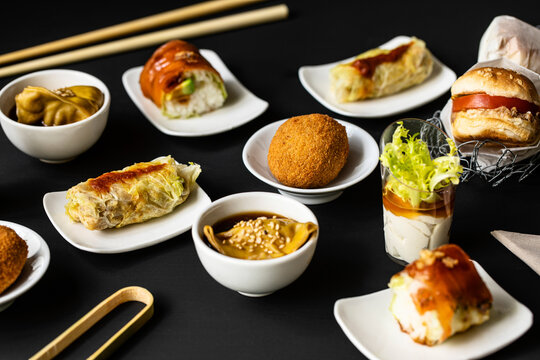 Top view of various tasty fusion food arranged on black table in restaurant