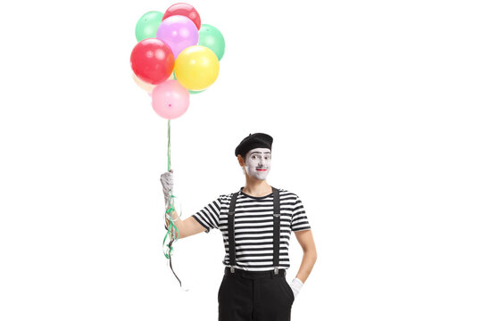 Mime standing with a bunch of balloons