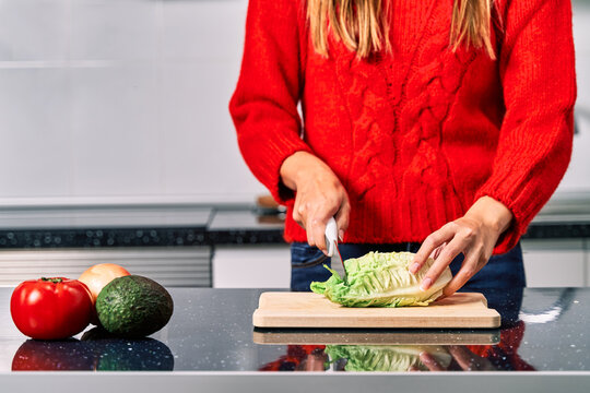 Crop faceless female cook cutting lettuce while preparing healthy vegetarian salad in kitchen