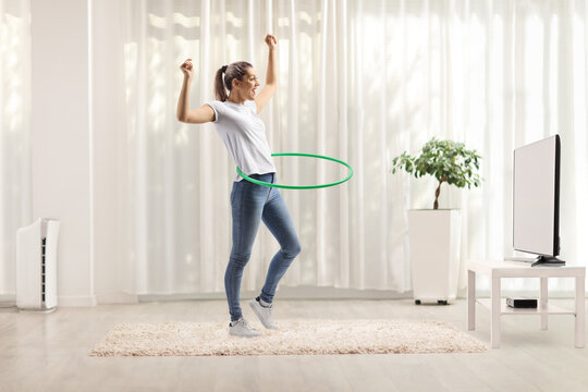 Young woman spinning hula hoop at home in a living room
