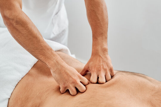 Unrecognizable male physiotherapist massaging back of patient lying on medical table during rehabilitation process in clinic