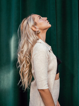 Side view of female with long blond hair and in stylish outfit standing near green building in city and looking away