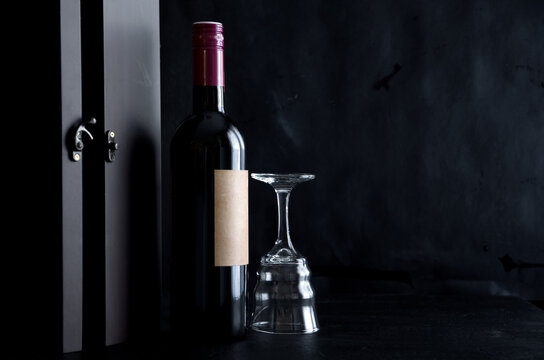 Old Bottle of Red Wine with Wood Box and Glass on Dark Background