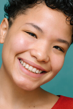 Portrait of young Latina woman with Asian eyes looking at the camera and smiling, close-up, isolated vertical photo, tidewater green background