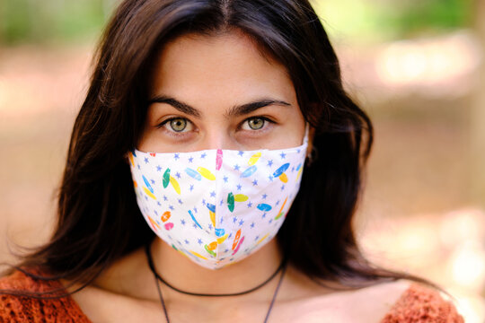 Confident young long haired brunette in colorful cloth protective mask for coronavirus prevention looking at camera while standing against blurred background of autumnal park