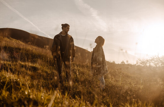 Loving couple in stylish retro clothes standing in field at sundown looking at each other