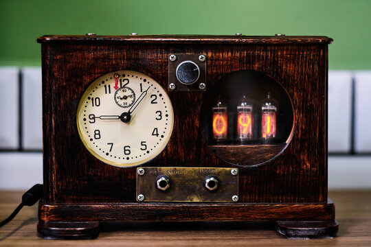 Vintage wooden steampunk clock with lamp indicators and round dial  placed on table