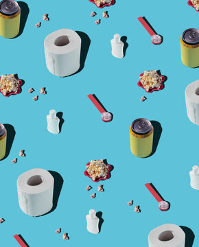 From above of patterns of hygiene supplies and soda cans on blue background with popcorn