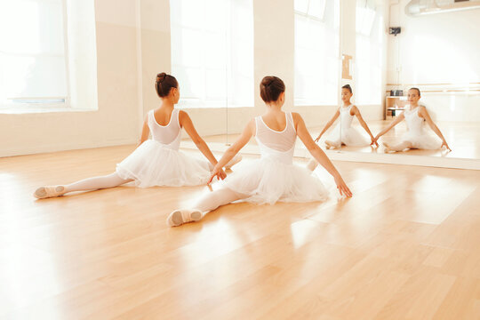 Back view of teen ballerinas sitting in splits on floor and looking in mirror while stretching in dance hall
