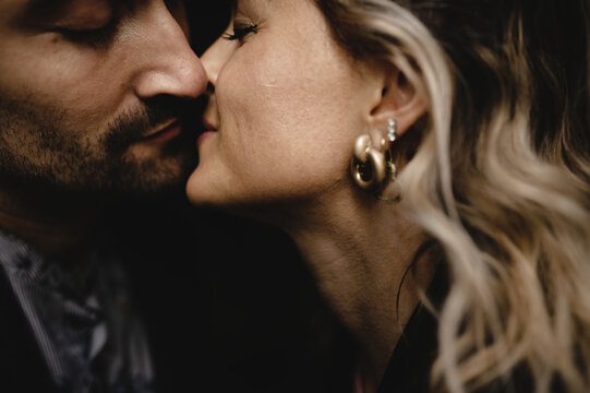 Side view of crop adult man and woman enjoying romantic moments together and kissing tenderly with eyes closed