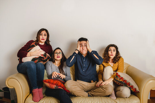 Group of scared friends gathering on sofa and watching horror movie during weekend at home