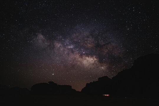 From below of glowing stars of Milky Way at night sky in Wadi Rum