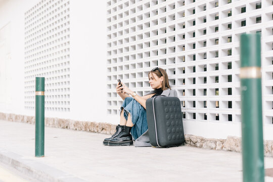 Side view of female tourist with luggage sitting alone on pavement and browsing mobile phone while getting lost in city