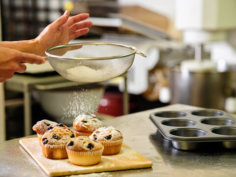 Side view of crop unrecognizable confectioner with sieve sprinkling sugar powder over freshly baked muffins with raisins while working in professional kitchen