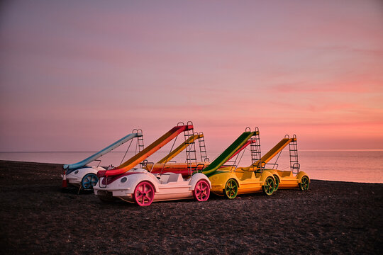 Collection of colorful pedal boats with slides placed on sandy beach on background of pink sunset over sea in Spain