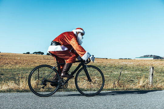 Side view of santa Claus in red costume riding modern bike along empty road in highlands on sunny day