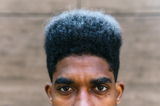 Crop determined African American male with dyed curly hair standing in city and looking at camera