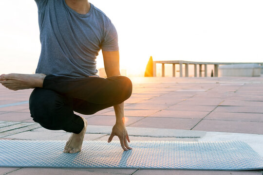 Unrecognizable crop male balancing in Toe Stand pose and doing yoga barefoot on mat at sundown in city