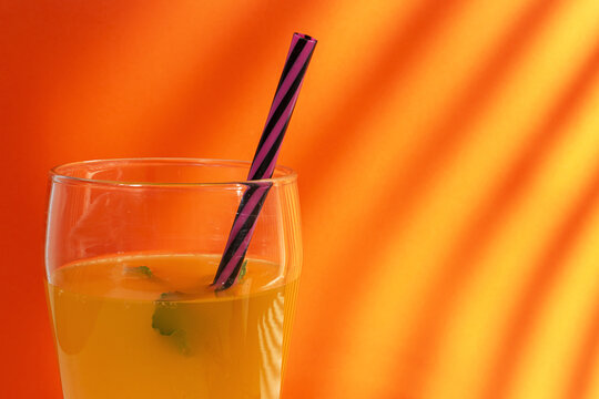 Glass of fresh fruit juice placed on orange background