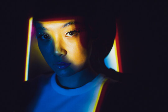 Young Asian female model with blond dyed hair and bright makeup looking at camera while standing in dark room illuminated by colorful neon lights