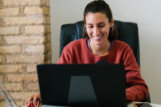 Happy young female in casual clothes smiling and browsing data on computer in cozy workspace