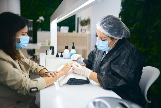 Side view of cheerful manicure master using nail file while sitting at table with female client in modern beauty salon during coronavirus pandemic