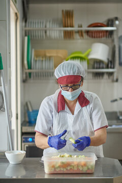 Female cook in white uniform and protective mask and gloves cutting fresh vegetables while preparing food in hospital kitchen during coronavirus pandemic