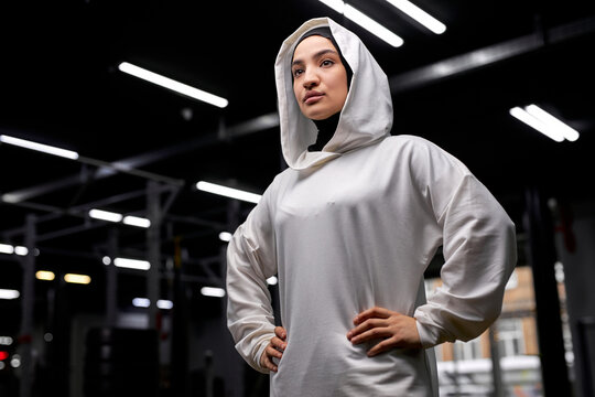 confident arabic muslim female in hijab posing after training, looking at side, wearing white sportive hijab, stands alone feeling power and stength, wellbeing concept