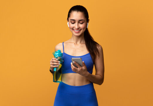 Sporty woman holding bottle with water using smartphone