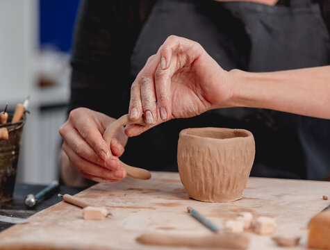 Hands of potter forming cup from clay
