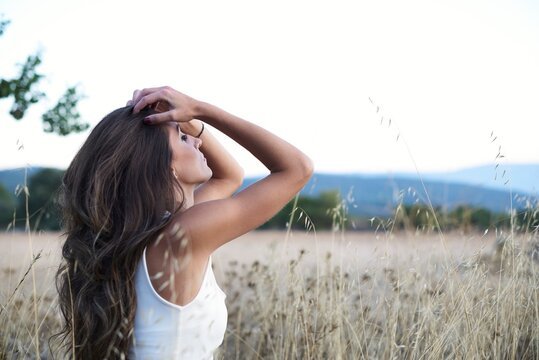 Side view calm slim brunette touching long hair sitting alone with eyes closed on meadow in countryside looking away in dreams