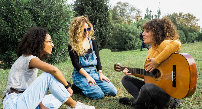 Group of cheerful multiracial female friends sitting on meadow in park and playing acoustic guitar while spending weekend together and looking at each other