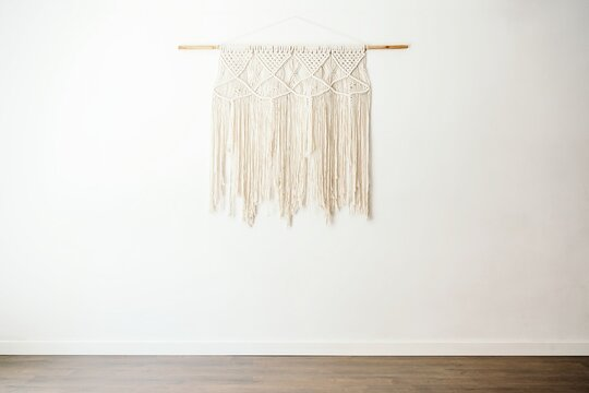 Eco friendly boho style cotton macrame decoration on wooden stick hanging on white wall in light room with minimalist interior