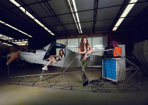 Female workers in front of plane plane fuselage and aircraft body frame in airplane hangar. Beautiful women in boilersuits posing for advertisement of small aviation. Welding machine behind the frame