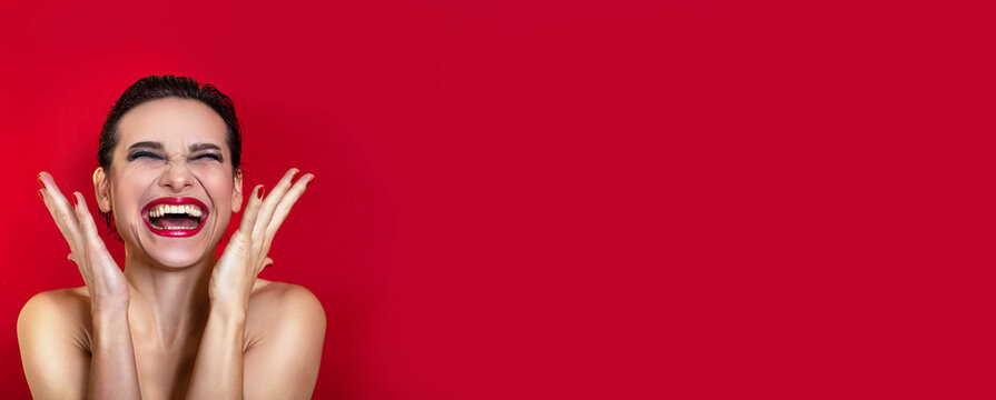 Horizontal banner. Woman with bright makeup shouting on red studio background. Copy space. Emotional fashion advertising card.