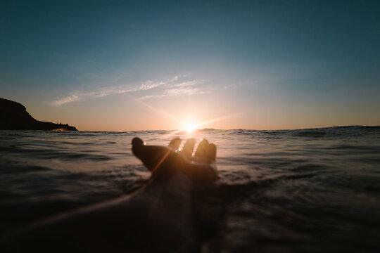 Crop anonymous person keeping hand over sea surface with calm water against shiny sun setting above horizon in evening