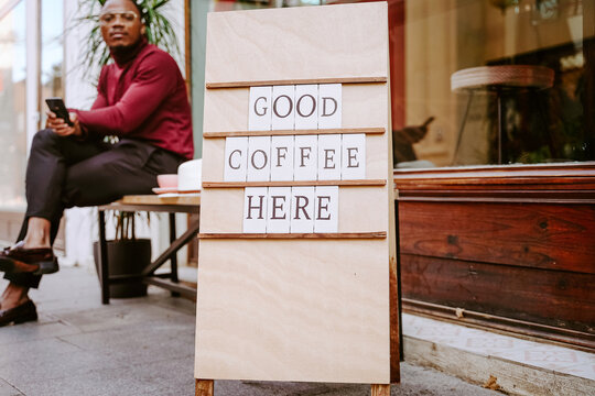Wooden board with inscription Good Coffee Here placed near coffee shop on background of Stylish African American male sitting on bench near coffee shop browsing on mobile phone on the street