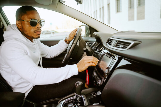 Side view of African American male driver sitting in luxury car and setting radio for listening to music