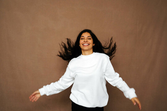 Positive ethnic female in white sweatshirt and with flying hair having fun in studio with closed eyes