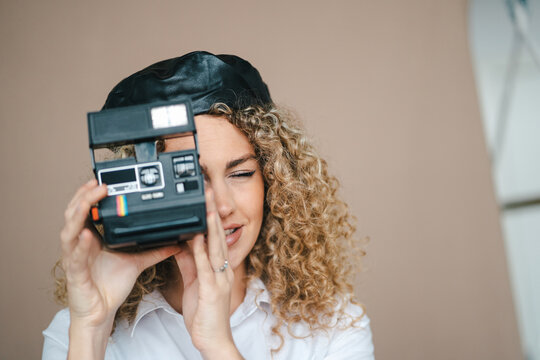 Female photographer with retro instant photo camera taking picture on brown background in studio