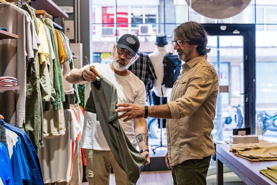 Side view clothing store owner helping new customer to choose a shirt