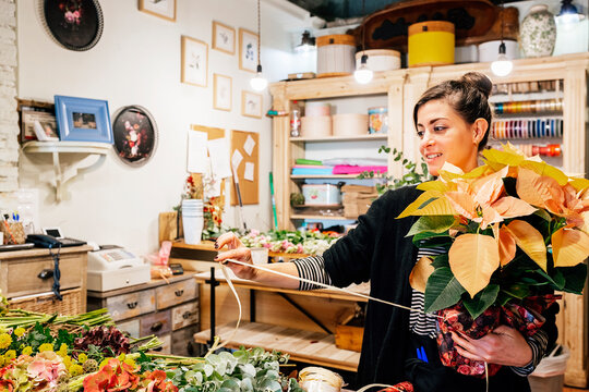 Professional female florist arranging christmas poinsettia flower bouquet while working in shop on wooden table