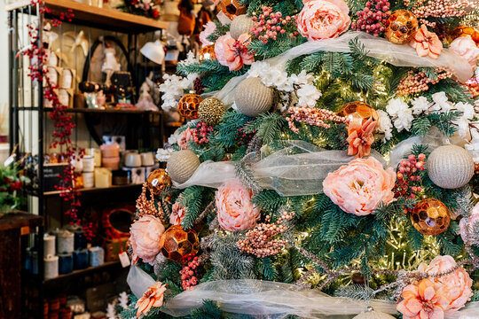 Beautiful christmas green artificial coniferous tree decorated with baubles, flowers and fairy lights ornaments