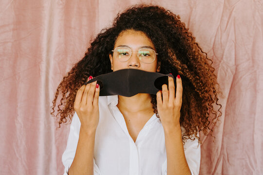 Young ethnic female with Afro hairstyle standing on pink background and putting on protective mask from coronavirus while looking at camera