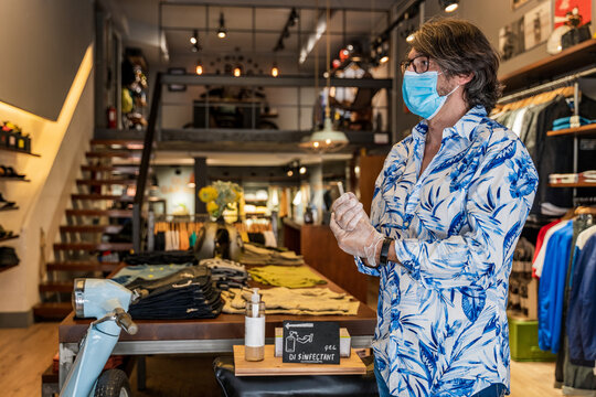 Side view of Customer with face mask and gloves shopping in a clothing store