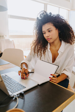 Modern young African American female remote employee in casual outfit sitting at table with laptop and writing in planner while working in home office